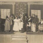 Fotografia przedstawia scenę, 17 osób. Aktorzy ubrani w stroje z epoki napoleońskiej: żołnierze, damy, arystokraci.