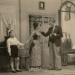 Fotografia przedstawia scenę, salonik. Kobieta trzyma za rękę chłopca, rozmawia z mężczyzną. Stroje z początku XX wieku.