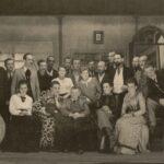Fotografia przedstawia scenę. Zdjęcie grupowe w kostiumach z początku XX wieku. Jeden rząd stoi, drugi siedzi: 15 mężczyzn, 6 kobiet.