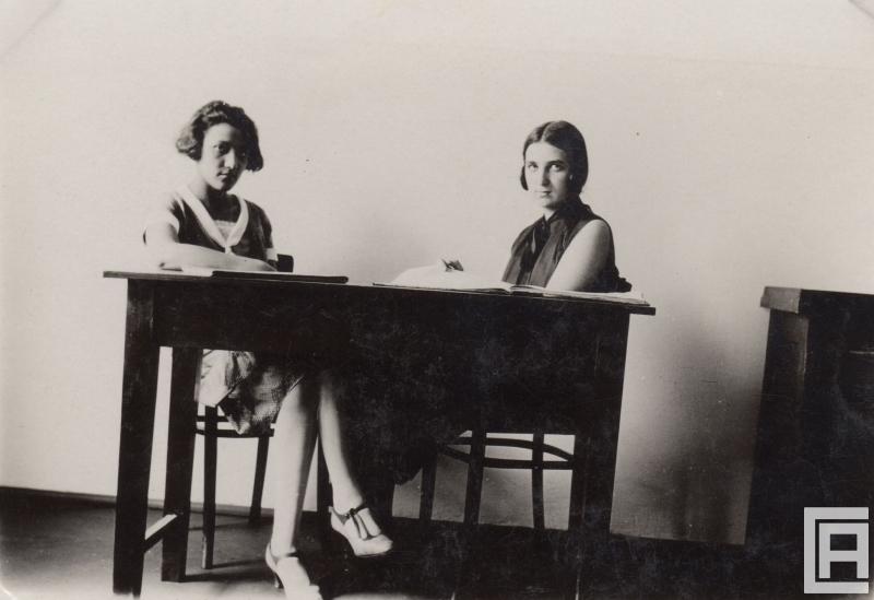 Fotografia przedstawiająca dwie młode kobiety siedzące przy biurku.