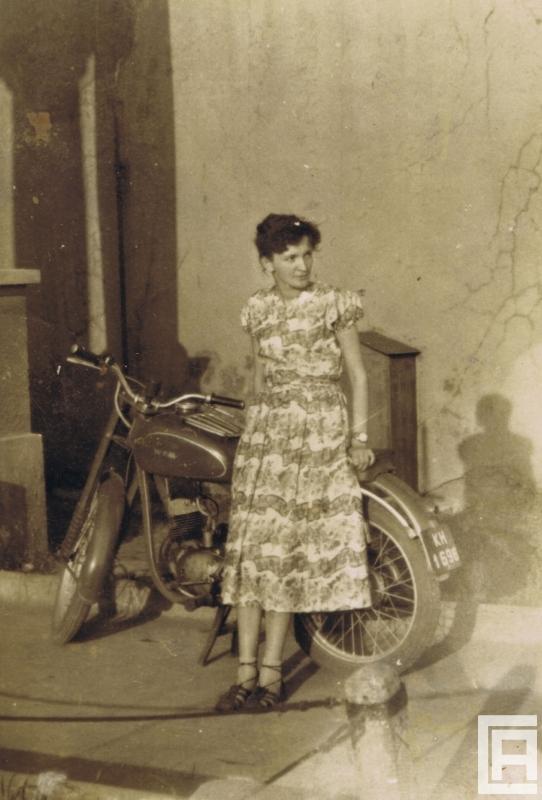 Fotografia przedstawiająca kobietę w sukience, która opiera się o motocykl.