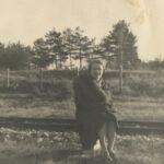 Fotografia przedstawia kobietę z futrem pozującą do zdjęcia przy torach kolejowych.