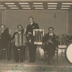 Fotografia przedstawia pięcioosobowy zespół w składzie: fortepian, akordeon, skrzypce, saksofon, perkusja.