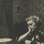 Fotografia przedstawia kobietę siedzącą przy stole, która opiera głowę na dłoni. W tle widoczny zegar ścienny.