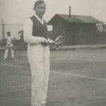 Fotografia przedstawia mężczyznę z rakietą tenisową. W tle widoczne: siatka, drugi gracz oraz drewniane zabudowanie.