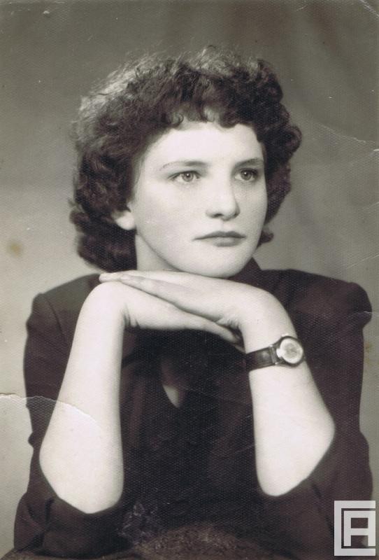 Fotografia przedstawiająca kobietę pozującą do zdjęcia, która opiera brodę na dłoniach.