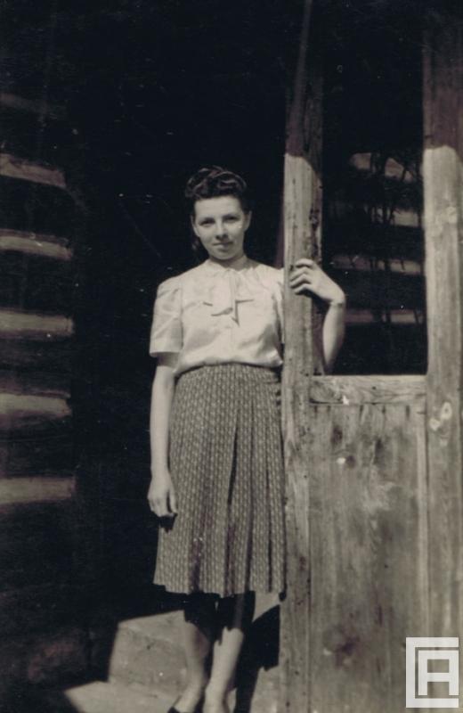 Fotografia przedstawiająca kobietę pozującą do zdjęcia przy domu.