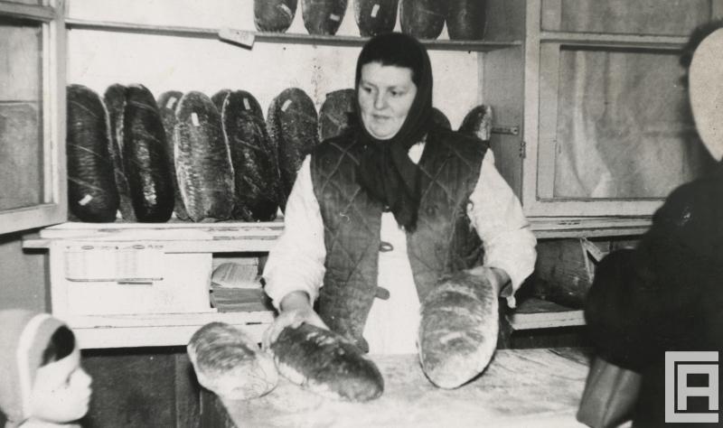 Fotografia sklepu z chlebem. Kobieta stoi za ladą trzyma 2 bochenki chleba. Za nią regał z chlebami. Przed ladą widoczni klienci.