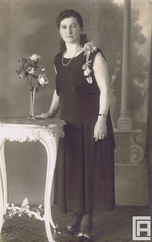 Stylizowana fotografia przedstawiająca kobietę przy stoliku z różami.