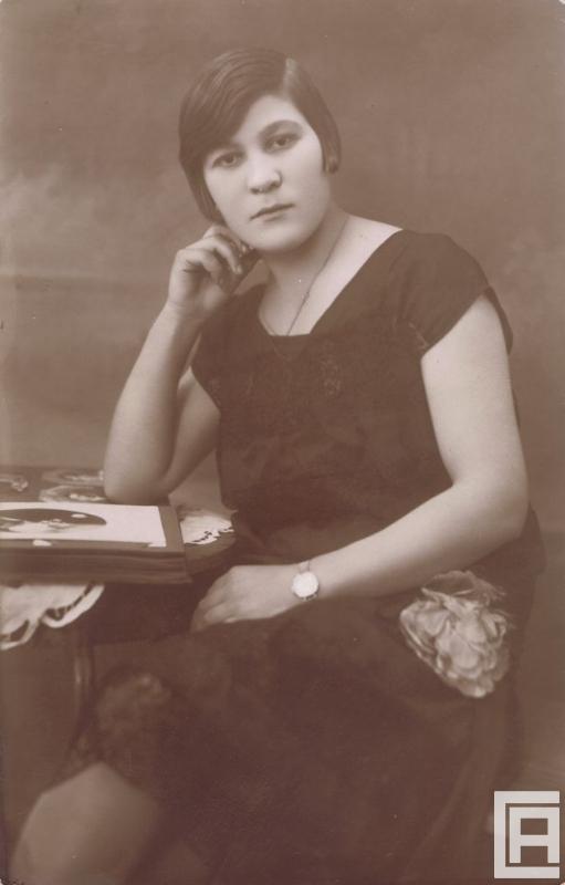 Stylizowana fotografia przedstawiająca kobietę przy stoliku z albumem.