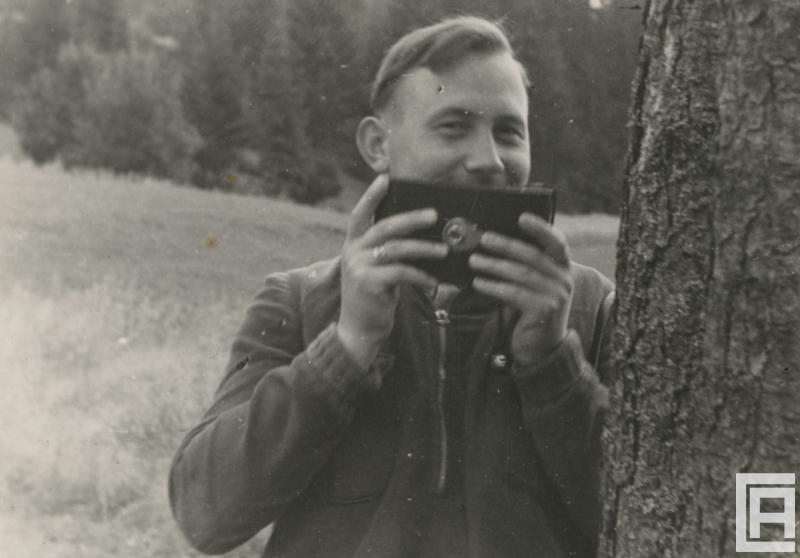 Fotografia przedstawia mężczyznę z aparatem fotograficznym.