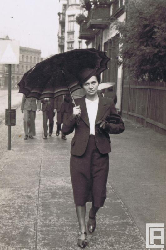 Fotografia przedstawiająca kobietę w kapeluszu, która idzie ulicą trzymając parasol.