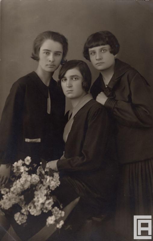 Fotografia przedstawiająca trzy młode kobiety pozujące z kwiatami.