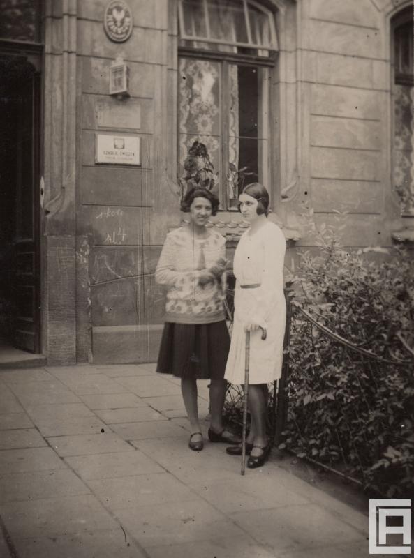 """Fotografia przedstawiająca dwie młode kobiety stojące przed budynkiem, ta z prawej trzyma laskę. Na ścianie widoczna tabliczka z godłem polskim i napisem """"Szkoła ćwiczeń""""."""