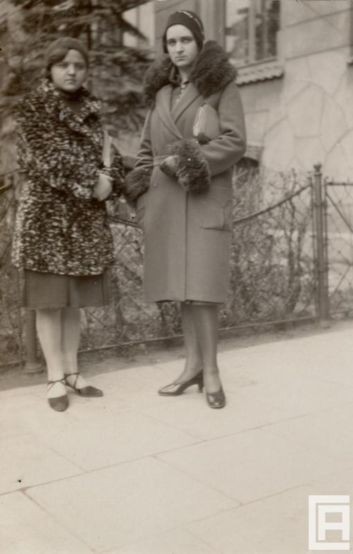 Fotografia przedstawiająca dwie młode kobiety stojące przed budynkiem, ta z prawej ma płaszcz wykończony futrem.