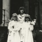 Fotografia przedstawia dwie dziewczynki w strojach komunijnych w towarzystwie dorosłej kobiety.