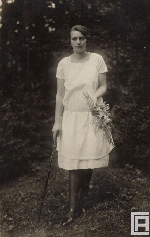 Fotografia przedstawiająca młodą kobietę w białej sukience, która w jednej ręce trzyma laskę, a w drugiej bukiet kwiatów.