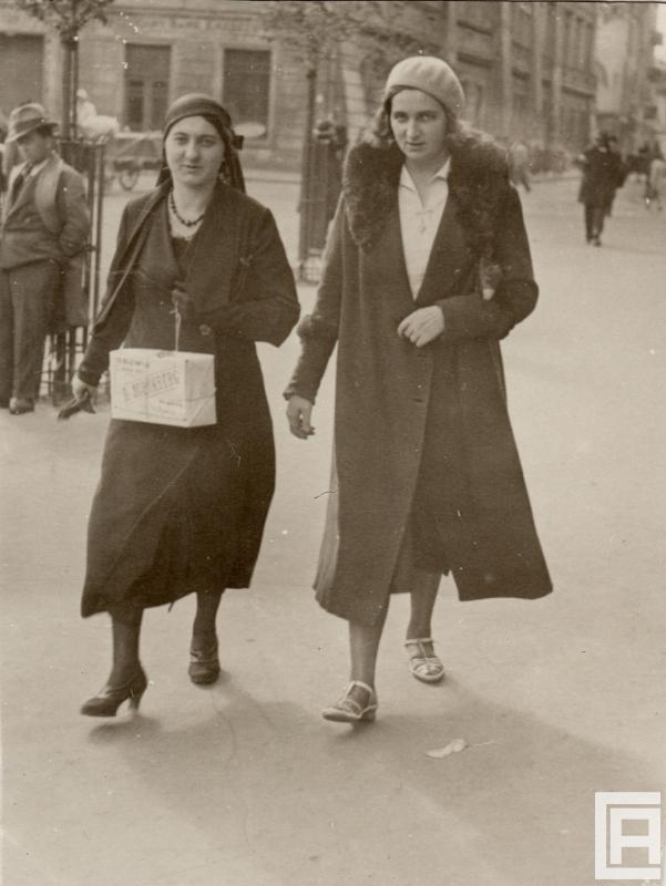 Fotografia przedstawiająca dwie młode kobiety idące przez miasto, ta z lewej niesie paczkę.