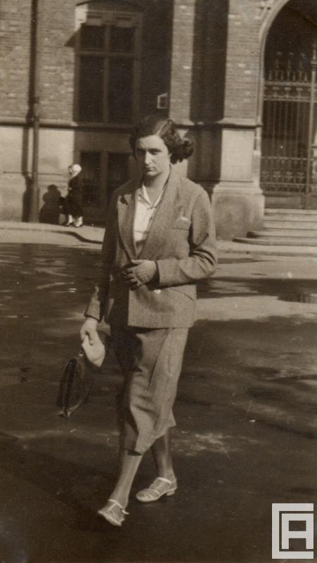 Fotografia przedstawiająca młodą kobietę idącą przez miasto, w prawej ręce niesie teczkę.