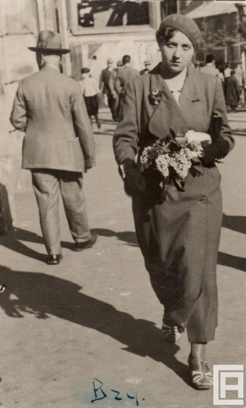 Fotografia przedstawiająca młodą kobietę w berecie idącą przez miasto, która niesie kwiaty.