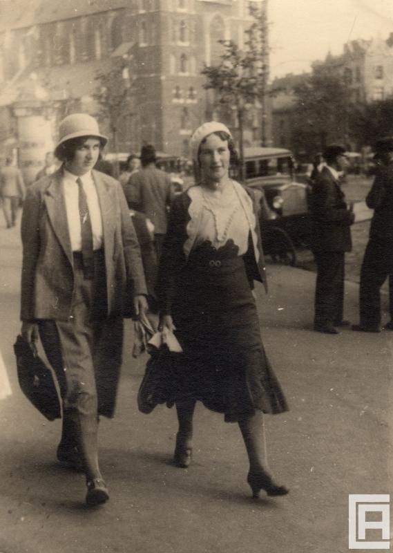 Fotografia przedstawiająca dwie młode kobiety idące przez miasto. Ta z lewej ubrana jest po męsku w garnitur i kapelusz. W tle widoczny Kościół Mariacki w Krakowie.
