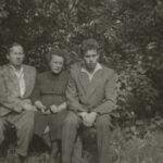 Fotografia przedstawia mężczyznę, kobietę i młodzieńca siedzących na ławce. W tle zieleń.