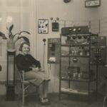 Fotografia przedstawia kobietę siedzącą przy stacji do nasłuchu krótkofalowego.