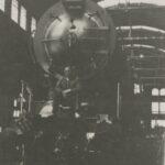Fotografia przedstawia mężczyznę w hali fabrycznej, który siedzi przed lokomotywą.