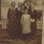Fotografia przedstawia grupę sześciu osób pozującą do zdjęcia przed namalowanym tłem.