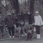 Fotografia przedstawia sześć kobiet w towarzystwie psa i dwóch mężczyzn-myśliwych z bronią palną.