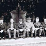 Fotografia przedstawia siedmiu mężczyzn siedzących na pniu. Za nimi widoczna rozpięta zwierzęca skóra.