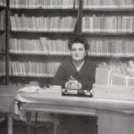 Fotografia przedstawia bibliotekarkę przy stanowisku. Za nią widoczne regały pełne książek.
