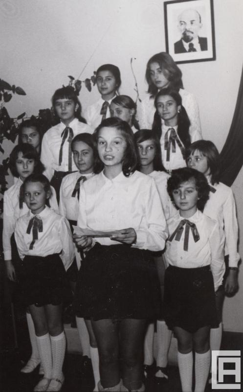Fotografia przedstawia odświętnie ubraną grupę dziewczynek. Nad nimi portret Lenina.