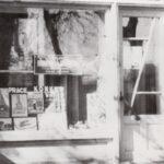 Fotografia przedstawia witrynę biblioteki wraz z tabliczką, obok drzwi.
