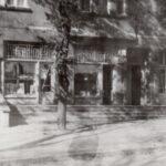 Fotografia przedstawia witrynę biblioteki wraz z tabliczką, obok drzwi. Widoczne otoczenie, chodnik i drzewa.