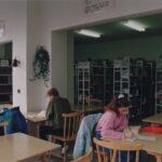 Fotografia przedstawia osoby czytające przy stolikach. W tle widoczne regały z książkami.