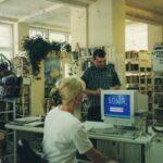Fotografia przedstawia bibliotekarkę przy komputerze obsługującą czytelnika.
