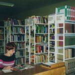 Fotografia przedstawia bibliotekarkę przeglądającą gazetę, za nią widoczne regały z książkami.