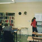Fotografia przedstawia czytelników przy stolikach.