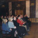 Fotografia przedstawia publiczność siedzącą na krzesłach.
