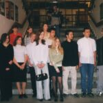 Fotografia przedstawia grupę osób stojącą przy schodach.