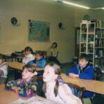 Fotografia przedstawia dzieci siedzące przy stolikach. W tle regały z książkami.