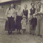 Fotografia przedstawia pięcioro dorosłych i troje dzieci przed wiejskim domem.
