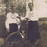 Fotografia przedstawia dwie kobiety w białych wyszywanych bluzkach. Jedna z nich prowadzi rower.