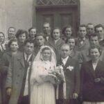 Fotografia przedstawia młodą parę i gości weselnych przed kościołem.