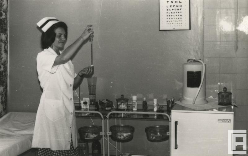 Fotografia przedstawia pielęgniarkę trzymającą termometr. W tle widoczny m.in. słój z wacikami, lodówka, tablica okulistyczna.