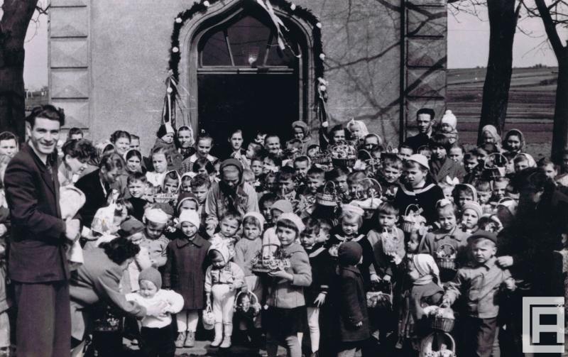 Fotografia przedstawia dorosłych i dzieci z koszyczkami wielkanocnymi przed kapliczką.