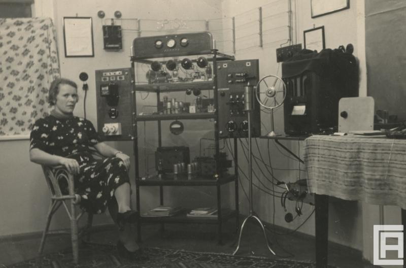 Fotografia przedstawia kobietę siedzącą na krześle obok urządzenia radiowego.