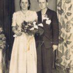 Fotografia przedstawia parę młodą pozującą do zdjęcia w studio. W tle kwieciste zasłony.
