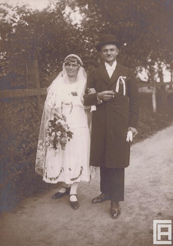 Fotografia przedstawia młodą parę pozującą do zdjęcia w plenerze.